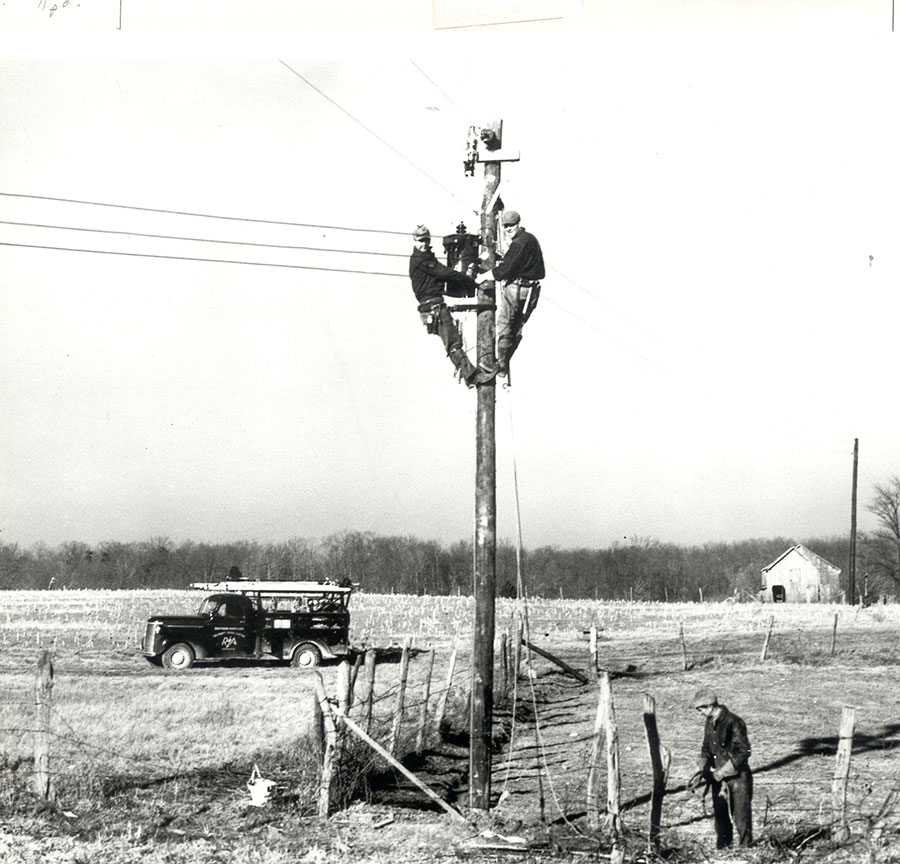 Old photo of linemen on top of a utility pole