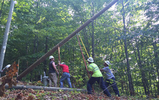 Workers setting a utility pole